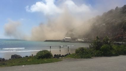 Dust from whitewash head cliff collapse near Sumner. Photo / Andrew Watson